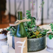 Table numbers on repurposed wine bottles.